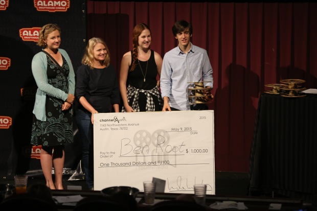 Ben Root poses along side the judges with an oversized check and 3 golden reels